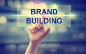 47808337 - hand pressing brand building on blurred cityscape background